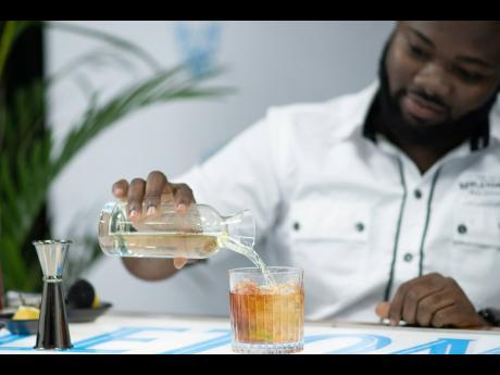 Mixologist at Appleton Estate, Randeen Thomas, expertly adds a touch of ginger ale to his glass, before completing Joy's Cocktail at the 'Home is Where the Rum is' virtual mixology session.