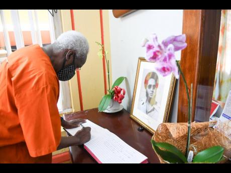 Former Prime Minister P.J. Patterson signs the condolence book for the late D.K. Duncan at the People's National Party headquarters on Tuesday.