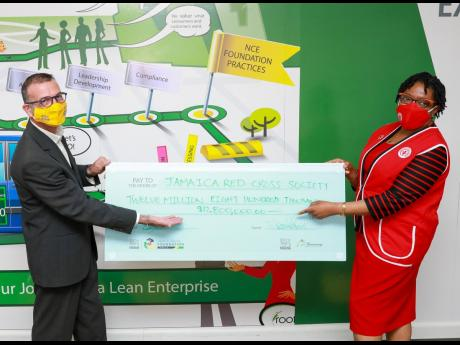 Nestlé Jamaica Limited Country Manager Daniel Caron (left) presents a symbolic cheque of $12,800,000 to President of the Jamaica Red Cross Society Hope Monroe at the recent signing of the partnership of the two entities to aid in the fight against COVID-1