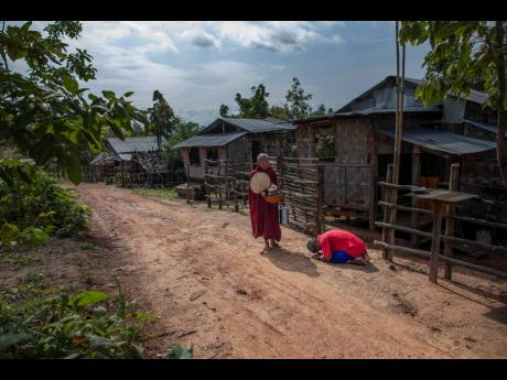 Zin Ko Ko Htwe, who was trafficked twice, bows after offering alms to a Buddhist monk outside his mother's house in Myawaddy, Myanmar, on Friday, June 14, 2019. Ko Htwe said after escaping from a fishing boat in 2008, he was sold on to a palm oil plantat