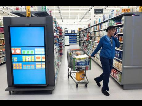 A customer pulls her shopping cart past an information kiosk at a Walmart Neighborhood Market, on April 24, 2019, in Levittown, NY. Kiosks and signs throughout the store keep customers informed that they are shopping in an artificial intelligence factory.