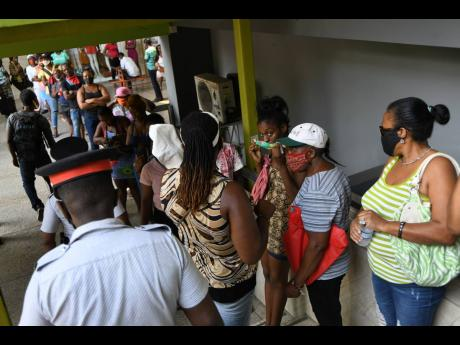 Police officers attempt to get a crowd at Western Union offices at the Pavilion Mall to observe social-distancing protocols in May. There have been concerns raised about the adherence of COVID-19 protocols, especially mask wearing and social distancing, a