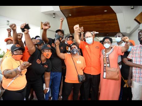 Mark Golding pumps his fist alongside is flanked by Joan Gordon Webley (third right) and Andrea Brown Burke shortly after the end of the PNP National Executive Council at the Jamaica Conference Centre on Sunday.