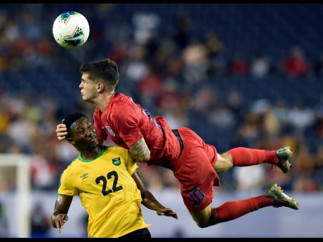 United States midfielder Christian Pulisic heads the ball above Jamaica midfielder Devon Williams (left) during the second half of a Concacaf Gold Cup semifinal match in Nashville, Tennessee on Wednesday, July 3, 2019.