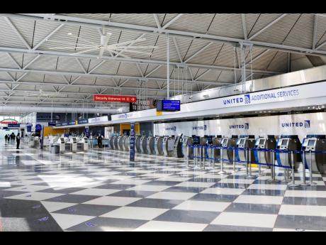 In this June 25, 2020 file photo, rows of United Airlines check-in counters at O'Hare International Airport in Chicago are unoccupied amid the coronavirus pandemic. About 40,000 workers in the airline industry are facing lay-offs as of Thursday, October