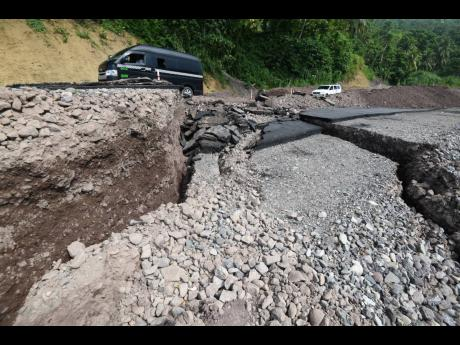 A minibus traverses past the collapsed roadway between Broadgate and the Westmoreland Bridge on Tuesday. Heavy rainfall has been blamed by local authorities for the damage but the National Works Agency has acknowledged that that section of the corridor had
