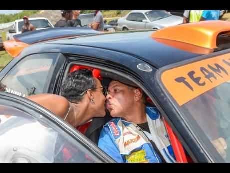 Driver Ian Banks gets a kiss from his wife Kedesha after completing a gruelling race at Dover.