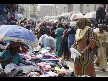 Pedestrians shop in a roadside market in Lagos, Nigeria.