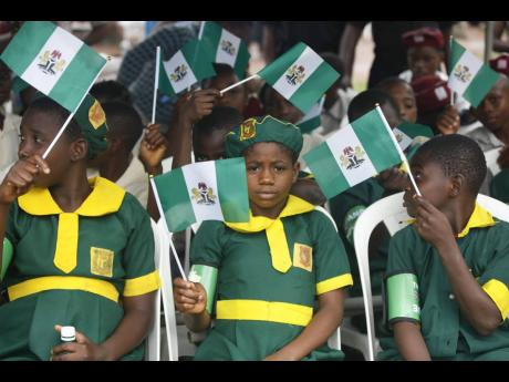 School children wave flags during the 54th anniversary in 2014 celebrations of Nigerian independence in Lagos, Nigeria.