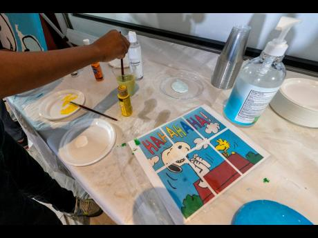 Jesse McCarty, 14, cleans his brush next to a diagram of a 'Peanuts' mural he is helping to paint that will be placed in the outpatient paediatric floor of One Brooklyn Health at Brookdale Hospital.