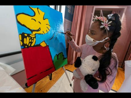 """Kaley Williams, eight, paints a panel of a """"Peanuts"""" mural that will be placed in the outpatient paediatric floor of One Brooklyn Health at Brookdale Hospital, Thursday, October 1, 2020, in the Brooklyn borough of New York."""