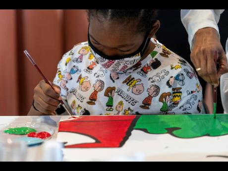 Kerrin McCarthy, 14 , paints a panel of a 'Peanuts' mural that will be placed in the outpatient pediatric floor of One Brooklyn Health at Brookdale Hospital.