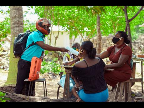 Contributed  Residents of Little Bay in Westmoreland collect their children's schoolwork from Keron King, principal of Little Bay Infant and All-Age School.