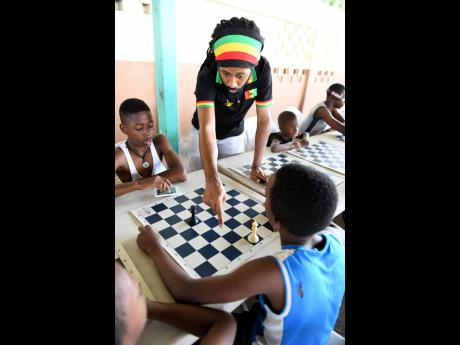 Instructor Malaku Lorne (top), of the Chess Whiz Kids Academy, explains how to move the king at the National Housing Trust Social Development Department's Introduction to Chess initiative on Wednesday, March 6, 2019.
