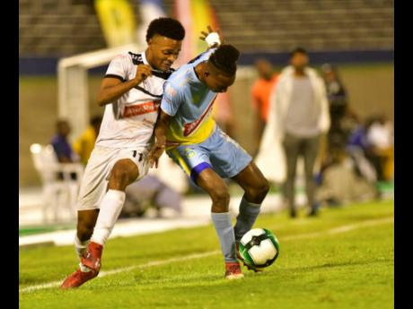 Ricardo Thomas (right) of Waterhouse fights to retain possession against Cavalier's Alex Marshall in the Red Stripe Premier League semi-final at the National Stadium on Monday, April 15, 2019.