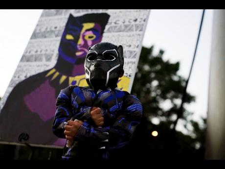 AP Mason Wilkes, 4, of South Carolina, poses for his father in a Black Panther costume, in front of a painting during a Chadwick Boseman Tribute on Thursday, September 3, 2020, in Anderson, South Carolina.
