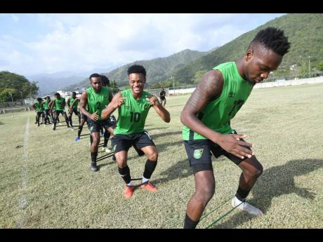 Members of Jamaica's national senior football team, the Reggae Boyz, are taken through a stretching exercise during a training session at The University of West Indies (UWI)/Jamaica Football Federation/Captain Burrell Centre of Excellence at UWI on Tues
