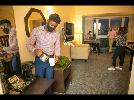 A group of professionals enjoy the amenities of a suite at The Jamaica Pegasus hotel in New Kingston. The capital city's landmark hotel has converted some of its rooms as co-working spaces under the newly launched CO(ME) Work initiative.