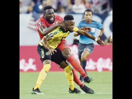 Jamaica forward Junior Flemmings (foreground) comes under a challenge from United States forward Jozy Altidore during a Concacaf Gold Cup semi-final football match in Nashville, Tennessee, on July 3, 2019.