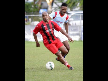 Former national footballer Wolde Harris turns away from his marker during their Bob Marley One Love exhibition football match at Winchester Park in Kingston on Monday, October, 15, 2018.