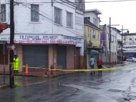 Police investigators at a crime scene along Strand Street in downtown Montego Bay, where Melaki Walters was chased and shot dead by gunmen yesterday.
