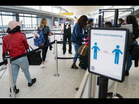 US Transportation Security Administration personnel and travelers observe COVID-19 transmission prevention protocols as acrylic dividers are employed to further protect staff working a Terminal 5 security checkpoint at John F. Kennedy International Airport