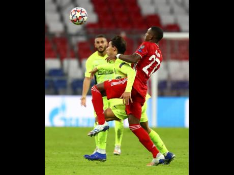Bayern Munich's David Alaba (right) and Atletico Madrid's Joao Felix battle for the ball during the Champions League Group A match between Bayern Munich and Atletico Madrid at the Allianz Arena in Munich, Germany, yesterday. Bayern won 4-0.