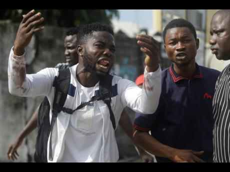 Alister, a protester who says his brother Emeka died from a stray bullet from the Army, reacts while speaking to Associated Press near Lekki toll gate in Lagos, Nigeria.