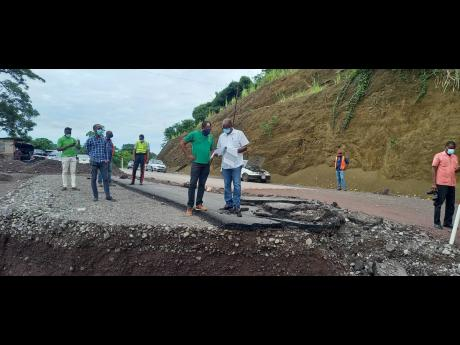 Government Minister Everald Warmington (centre, right) and St Mary South Eastern Member of Parliament Dr Norman Dunn discussing aspects of design crafted by NWA technical personnel for the reconstruction of the collapsed roadway at Chovey in St Mary during
