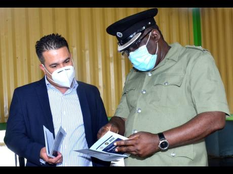 Minister without Portfolio in the Ministry of National Security, Senator Matthew Samuda (left), peruses a programme with Superintendent, Tamarind Farm Adult Correctional Centre, Leslie Campbell. Occasion was a ceremony held on Thursday to officially commis