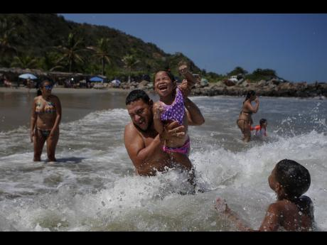 Caracas resident Jose Velasco lifts his daughter, Ashley Velasco, above a wave off La Ultima beach after it recently reopened following a lockdown to contain the spread of COVID-19 in La Guaira, Venezuela, on Friday.