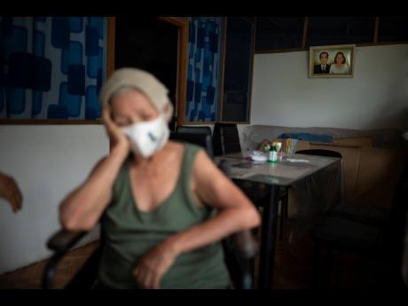Suffering from a high fever related to dengue, 72-year-old Luz Rengifo rests inside her home in Pucallpa, Peru, on Tuesday.