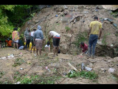 The residents of Shooters Hill in St Andrew working feverishly to dig through debris for a missing 15-year-old student of The Queen's School whose father's body was found after a landslide yesterday fell on the house they were in.