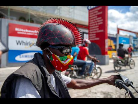 A motorcyclist wears a protective face mask and a mohawk helmet as he takes part in a protest to demand the resignation of President Jovenel Moise in Port-au-Prince, Haiti, Saturday, Oct. 17, 2020. The country is currently experiencing a political impasse