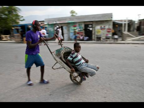In this December 2019 photo, a young man pushes a wheelbarrow home as his little brother takes a ride on it, in the Cite Soleil slum of Port-au-Prince, Haiti. The two youths are going home after helping their mother by carrying items to sell in the market.