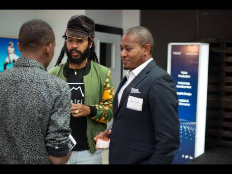 INDIGGO Conference: Reggae artiste Protoje (centre) and Minister of Agriculture and Fisheries Floyd Green (right) speak to a patron at the virtual arthouse exhibition at last year's staging of the INDIGGO Conference.