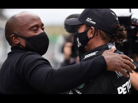 Mercedes driver Lewis Hamilton (right) of Britain is congratulated by his father Anthony Hamilton after his record-breaking win during the Formula One Portuguese Grand Prix at the Algarve International Circuit in Portimao, Portugal, yesterday.