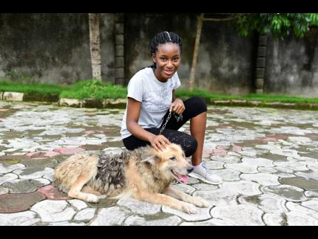 In this photo taken on Wednesday, October 14, 2020, Dodeye Ewa, 16 years old, plays with a dog outside her compound in Calabar, Nigeria. The third child is bothered by President Donald Trump's rhetoric and his policies towards international students, mos