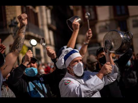 In this Friday, October 16, 2020 file photo, workers of catering sectors take part in a protest organised by restaurants and bar owners in Barcelona, Spain.