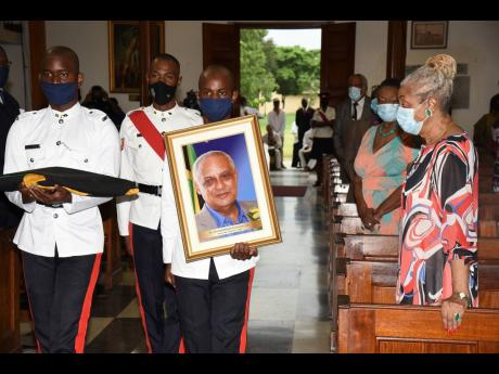 Police Sergeant Kevin Wallace (second right) marches past Beverley Anderson Duncan (right), widow of Dr D.K. Duncan, with his photograph during the funeral at the University Chapel in Mona, St Andrew, on Sunday. Also marching are trainee constables André
