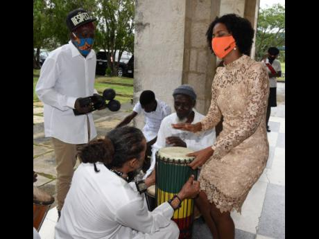 Imani Duncan-Price, daughter of the late Dr D.K. Duncan, plays the drum alongside members of Akwaaba and Mystice Revelation as they  performed outside the University Chapel in Mona during Duncan's funeral on Sunday.
