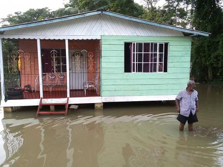 Gladstone Wollery, a resident of Three Miles River in Westmoreland, up to his knees in floodwaters that covered several yards in the community on Sunday.