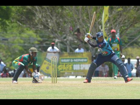 Johnson Mountain batsman Jair Campbell (right) steadies himself for a shot while Gayle wicketkeeper Anthony Walters looks on during their Social Development Commission Wray & Nephew Community Twenty20 Cricket competition at the Ultimate Cricket Oval in St