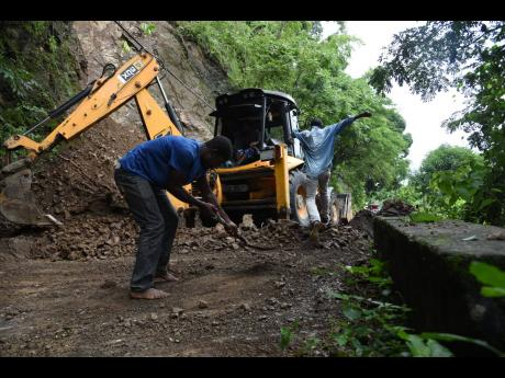 A man, with the help of a tractor, clears a land slippage that blocked the Mount Felix main road in St Thomas on Monday after heavy rains battered the island on the weekend.