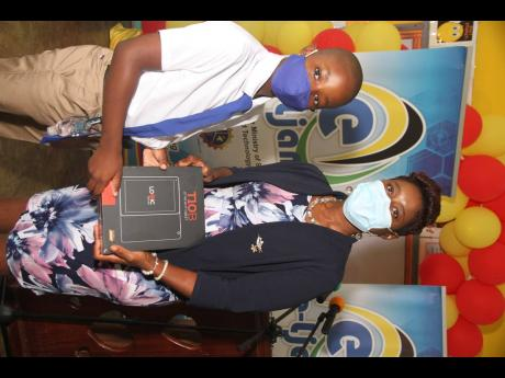 Darnell Smith and his Principal Tina Reid-Green of Mocho Primary and Infant School in Clarendon display the tablet handed over to the student by e-Learning Jamaica on October 29.
