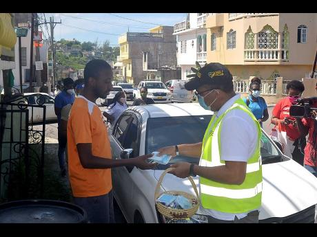 Health Minister Dr Christopher Tufton (right) hands out packets of face-masks to a resident of Cornwall Courts in St James during a walk-through of the community on Friday. Cornwall Courts hasbeen under a special curfew since October 23, following an inc