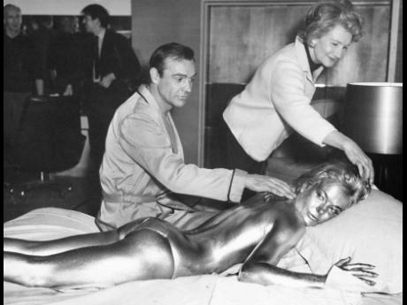 In this file photo dated April 20, 1964, James Bond, alias, Sean Connery, finds himself in a sticky situation with actress Shirley Eaton at Pinewood Studios, near London.  Miss Eaton was given a liberal coating of gold paint for a scene in the latest Bond