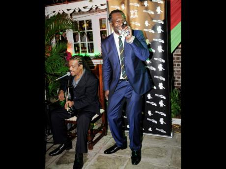 Levi Roots (right) performs at the official opening of his Levi Roots Store, held at Devon House on November 5, 2013. He is accompanied on the guitar by Dalton Browne.