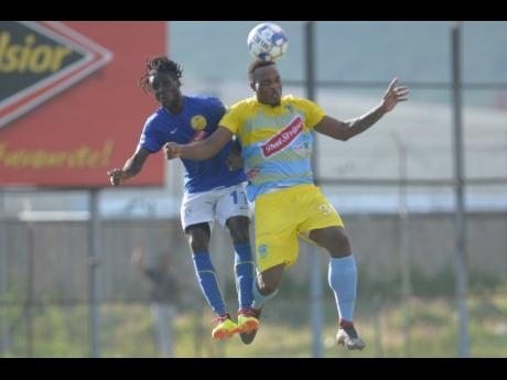 Waterhouse's Shawn Lawes (right) goes up for an aerial challenge with Vere's Devroy Grey during a Red Stripe Premier League match last season.