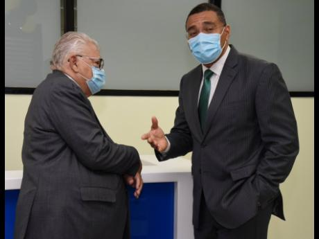 Prime Minister Andrew Holness (right) and Karl Samuda, minister of labour and social security, share a moment during the official opening of Samuda's ministry's parish office in St Ann's Bay, St Ann, on Thursday.